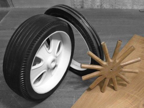 Rueda. Corte de ambos lados para armar cubierta y llanta. Rayos tallados a mano en cedro - Wheel. Both sides cut to assemble tire and rim. Wooden spokes hand carved from cedar
